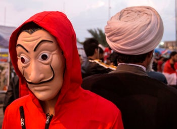 Iraqi protester in a Money Heist outfit stands behind a Shiite Muslim cleric during an anti-government demonstration, Basra, November 29, 2019