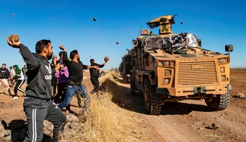 Kurdish demonstrators hurl rocks at a Turkish military vehicle during a joint Turkish-Russian patrol near the town of Al-Muabbadah, Syria, November 8, 2019.