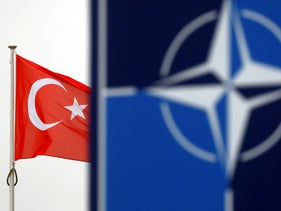 A Turkish flag flies next to NATO logo at the Alliance headquarters in Brussels, Belgium, November 26, 2019