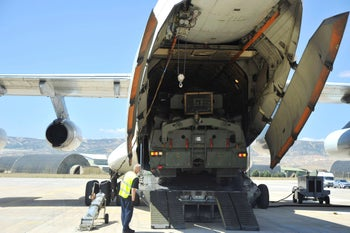 Military officials by a Russian transport aircraft, carrying parts of the S-400 air defense systems, after it landed at Murted military airport outside Ankara, Turkey. Aug. 27, 2019