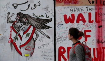 A woman looks at a wall at United Nations Headquarters, decorated with graffiti in Arabic that reads, 'Revolution is a woman,' and 'Oh freedom,' in Beirut, Lebanon, November 26, 2019.