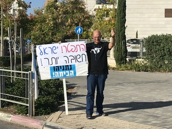 """Amir Haskel standing at one of his regular protest spots in his hometown of Yavneh, November 29, 2019. His sign says """"Resign! Israel is more important! Netanyahu, go home!"""""""
