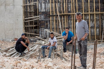 Mohammad Abu Ta'ah with family members - Ahmad, Mohammad and Mohanad (Right to left) next to the foundation of the Amana settlement organisation building which was build on the land expropriated from them, in 2016.