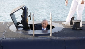 Benjamin Netanyahu climbs out after a visit inside the INS Rahav, the fifth submarine in the fleet, after it arrived in Haifa port January 12, 2016