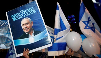Supporters of Prime Minister Benjamin Netanyahu chant slogans and hold up signs in support of him during a rally in Tel Aviv, November 26, 2019.