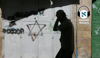 An Israeli settler walks past a Star of David graffiti on the door of a closed Palestinian shop in the Jewish settlement area of the West Bank city of Hebron in 2010.