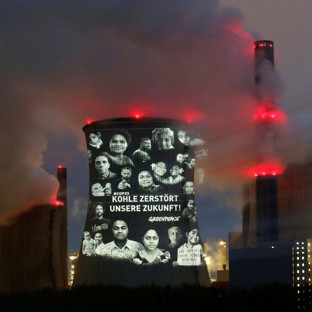 """Activists of the environmental organisation Greenpeace project a slogan that reads """"No Future in Fossil Fuels"""" on the cooling tower of RWE coal power plant, one of Europe's biggest electricity companies in Neurath, north-west of Cologne, Germany, November 10, 2017"""