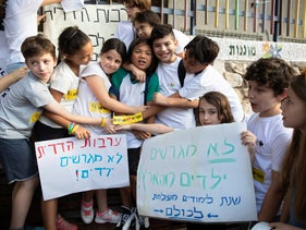 Children hug their classmate, slated for deportation to the Philippines, in a protest against deporting children, at Hillel School in Ramat Gan, September 1, 2019.
