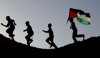 Palestinian youths, one carrying a Palestinian flag, run on a hillside after Israeli troops pulled out of Beit Lahiya, in the northern Gaza Strip, Sunday, Nov. 26, 2006