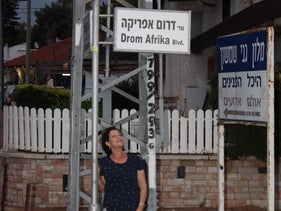 Ronit Zwebner next to a street sign indicating Ashkelon's South African roots.