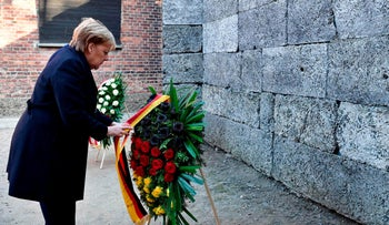 Angela Merkel arranges the ribbon of a wreath as she attends a wreath laying ceremony at the Death Wall, December 6, 2019.