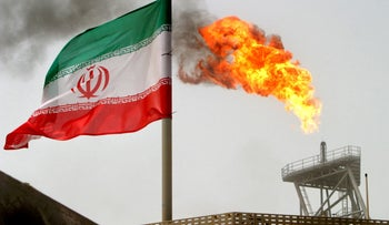 A gas flare on an oil production platform in the Soroush oil fields is seen alongside an Iranian flag in the Gulf July 25, 2005