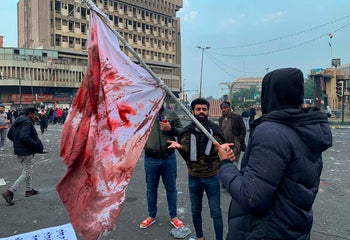 A protester holds a blood-stained flag at the site of a gunmen attack in Baghdad, December 7, 2019