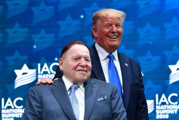 Donald Trump stands on stage with Sheldon Adelson ahead of his address to the Israeli American Council National Summit on December 7, 2019.