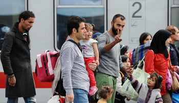 Migrants and refugees wait to board a train shortly after arriving in Munich, Germany, 2015.