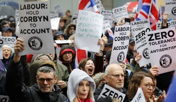 People hold up placards and Union flags as they gather for a demonstration organised by the Campaign Against Anti-Semitism outside the head office of the British opposition Labour Party in central London on April 8, 2018.
