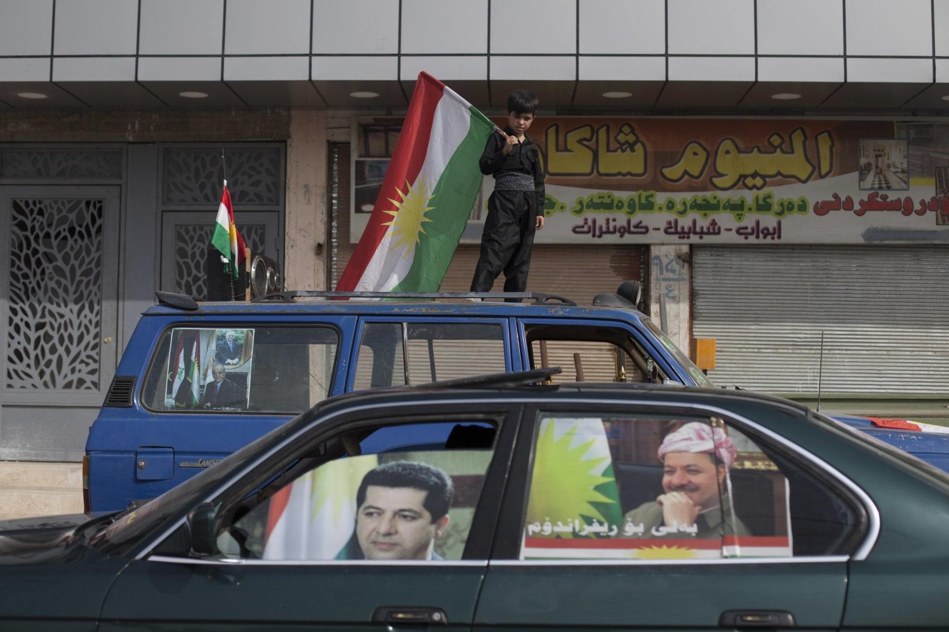 A boy carrying a Kurdish flag on top of a vehicle as a car with the faces of Kurdish President Masoud Barzani and his son Masrour on the windows passes by in the disputed city of Kirkuk, September 25, 2017.