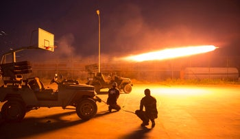 FILE PHOTO: Shi'ite fighters fire a rocket during clashes with Islamic State militants in Salahuddin province, Iraq, March 1, 2015.
