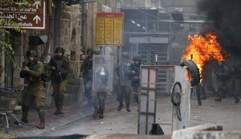 Israeli soldiers clash with Palestinian protesters in the southern West Bank city of Hebron, on December 9, 2019,