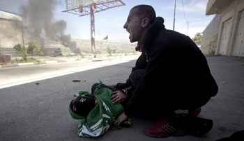 A Palestinian man shouts for help moments after teenager Mohammad Abu Daher was shot to death by Israeli troops near Ramallah, May 15, 2014