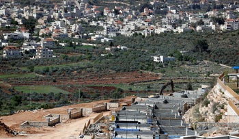 Turmus Ayya (background) and houses under construction in the Jewish settlement of Shiloh, West Bank, March 31, 2017
