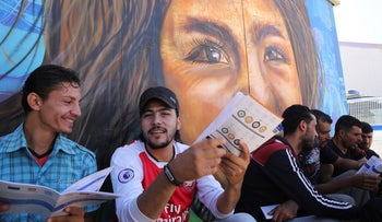 Syrian refugees read brochures during a EU-sponsored job fair in Zaatari, Jordan's largest camp for Syrian refugees