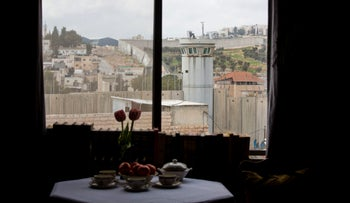 An Israeli security watch tower is seen from one of the rooms of the the Walled Off Hotel in Bethlehem, March 3, 2017.