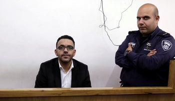 Adnan Ghaith and an Israeli policeman during a court hearing, 2018.