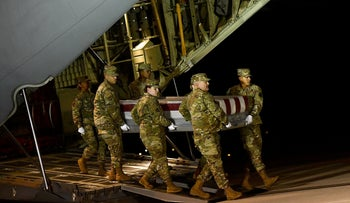 Military personnel carry a transfer case for fallen service member, U.S. Navy Ensign Joshua Watson, during a dignified transfer at Dover Air Force Base on December 8, 2019 in Dover, Delaware.