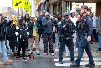 Bystanders look on as law enforcement arrive on the scene following reports of shooting, December 10, 2019