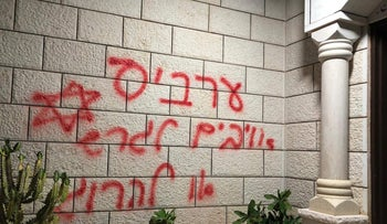 Hateful graffiti in Hebrew reading 'Arabs are enemies -- expel or kill,' and a Star of David spary-painted on a wall in Manshiya Zabda, northern Israel, December 12, 2019.