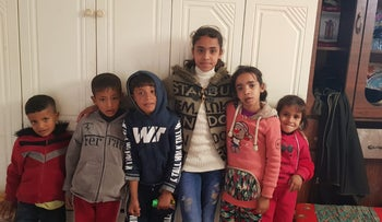 """Noor Sawarka, center, surrounded by surviving siblings and cousins. """"They took everything that was beautiful in my life away from me. We became orphans."""""""