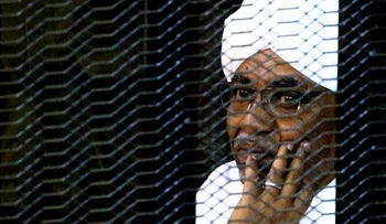 Omar al-Bashir sits inside a cage as he faces corruption charges in a court in Khartoum, September 28, 2019.