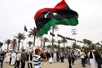 A Libyan man waves a Libyan flag during a demonstration to demand an end to the Khalifa Haftar's offensive against Tripoli, in Martyrs' Square in central Tripoli, Libya April 26, 2019.