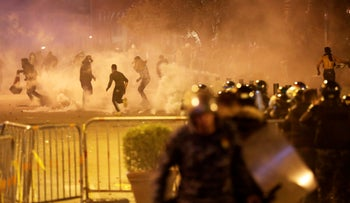 Anti-government protesters run away as the riot police fired tear gas against them during a protest in downtown Beirut, Lebanon, Saturday, Dec. 14, 2019.