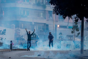 A supporter of Lebanon's Shiite Hezbollah and Amal groups gestures towards riot police during clashess in Beirut, December 14, 2019.