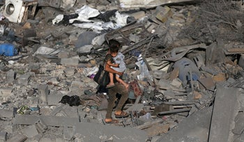 A Palestinian boy carries his brother as he walks through the debris of a house destroyed in an Israeli air strike in the southern Gaza Strip, November 14, 2019.
