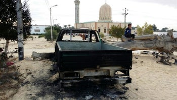 A burned truck is seen outside Al-Rawda Mosque in Bir al-Abd in the northern Sinai, Egypt a day after attackers killed hundreds of worshipers, on Saturday, November 25, 2017.