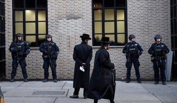 Orthodox Jewish men pass police guarding a Brooklyn synagogue prior to a funeral for the victim of a shooting at a kosher market, Dec. 11, 2019.