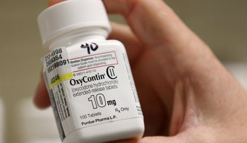 FILE PHOTO: A pharmacist holds a bottle OxyContin made by Purdue Pharma at a pharmacy in Provo, Utah, U.S., May 9, 2019.