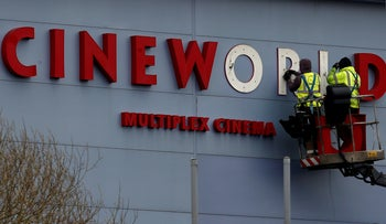 Workers repair a sign at a Cineworld cinema in Bradford northern England, March 24, 2016.