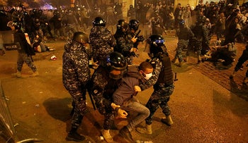 Riot police officers beat anti-government protesters during a protest near the parliament square, in downtown Beirut, Lebanon, December 15, 2019.