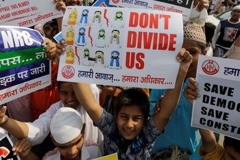An Indian Muslim boy holds a placard during a protest against Citizenship Amendment Bill after Friday prayers in Ahmadabad, India, Friday, Dec. 13, 2019