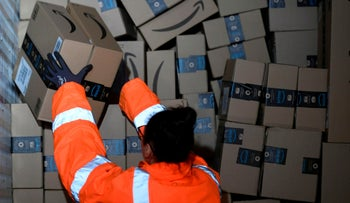 An employee places packed goods on a container at an Amazon distribution center in Moenchengladbach, Germany, December 17, 2019.