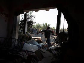 A Palestinian boy walks through a hole in a wall of a destroyed house following overnight Israeli missile strikes, in the town of Khan Yunis, southern Gaza Strip, November 14, 2019.