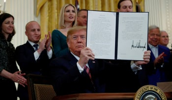 U.S. President Donald Trump holding up an executive order on anti-Semitism that he signed in the East Room of the White House, Washington, December 11, 2019.