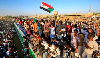 Sudanese protesters cheer upon arriving from the capital Khartoum to the town of Atbara, December 19, 2019.