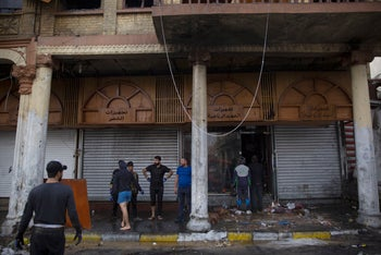 Iraqis clean a sports supplies store after the whole building caught fire during clashes between protesters and riot police in al-Rasheed street in Baghdad, Iraq,on Monday, December 16, 2019.