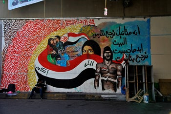 A protester sits by a mural in Tahrir Square during ongoing protests in Baghdad, Iraq, Thursday, Dec. 19, 2019.