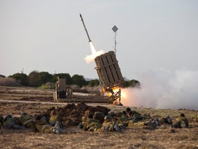 Soldiers take cover as the Iron Dome missile defense system launches a rocket to bring down a projectile fired from Gaza, in 2012.